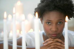 african american woman praying candles